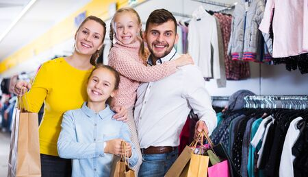 glad friendly family of four with shopping bags in clothing shop