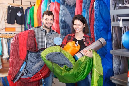Young loving couple demonstrating tourist equipment in sports clothes store. Focus on both persons
