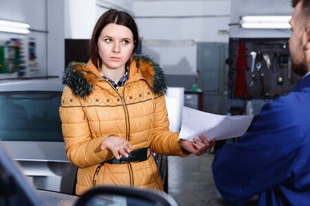 Young  woman client is dissatisfied of repair of her car in winter in workshop.