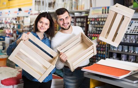 Young couple demonstrating boxes for decorating house in paint supplies store Imagens