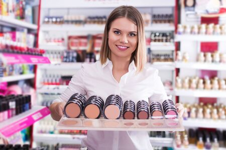young saleswoman helping to choose powder in beauty store