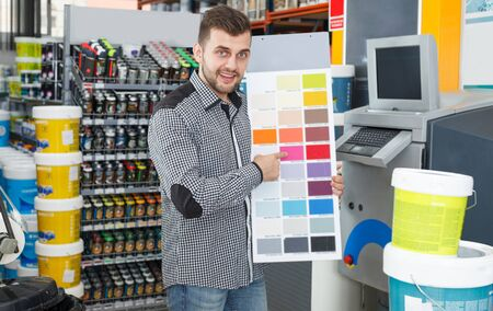 Cheerful young man looking samples of color at palette in household store