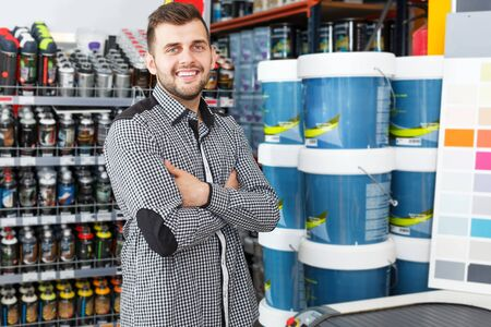 Emotional guy standing near shelfes with paints in paint store Imagens