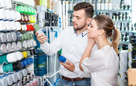 Young loving couple choosing paint spray together in paints store