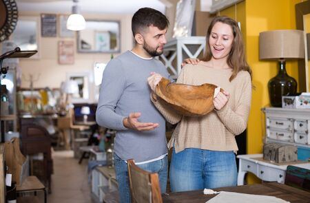 Young happy couple choosing vintage wooden platter in furnishings store