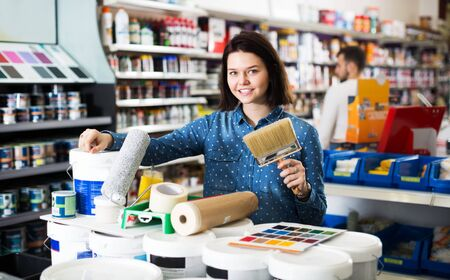 Young woman buying tools for house decoration in paint supplies store Imagens