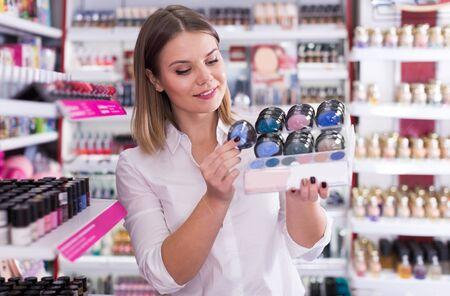 Young stylish woman choosing eyeshadows in cosmetics shop