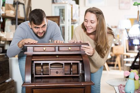 Happy girl with boyfriend choosing vintage cabinet in furnishings store 写真素材