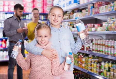 Two small happy sisters holding bottled water during family shopping in supermarket