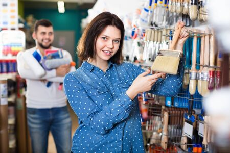 Positive female customer examining various painting brushes in paint supplies store Imagens