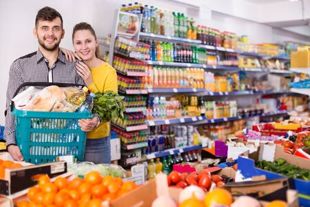 Happy young couple with variety of products in a shopping basket in store