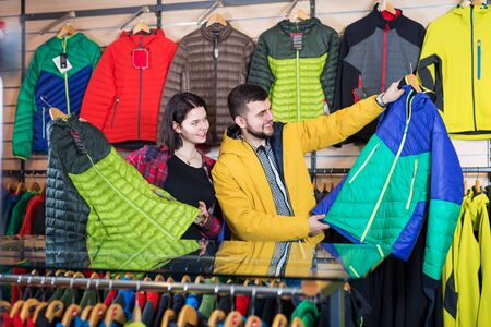 Glad couple examining windcheaters in sports clothes store