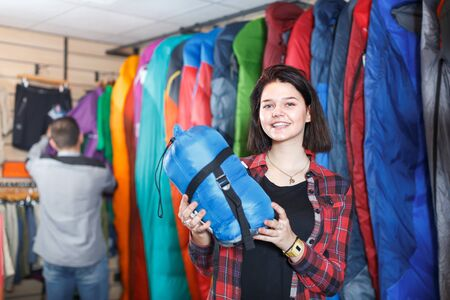 Young female customer examining sleeping bags in sports equipment store