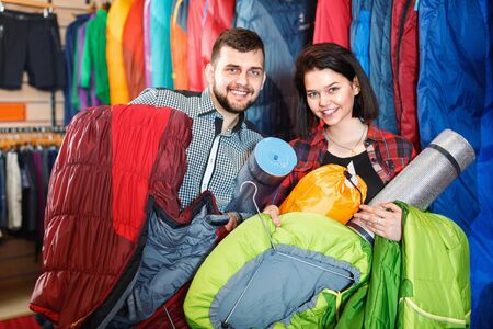 Young smiling couple choosing touristic equipment in sports equipment store