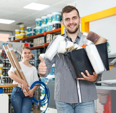 Joyful couple showing tools for house decoration in paint  store Imagens