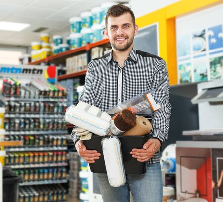 Positive man with purchases i standing in shelves with paints in household shop Imagens