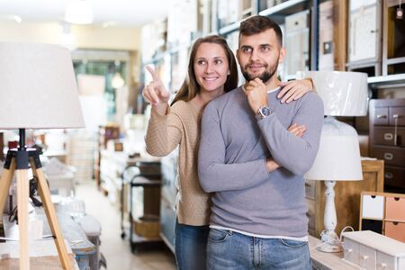 Portrait of attractive girl and her boyfriend in antique furnishings store