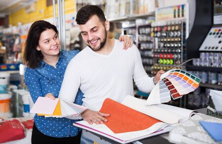 Young couple examining color scheme in paint supplies shop