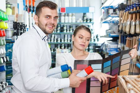 Happy man and woman  standing with tools using palette scheme in paint shop Imagens