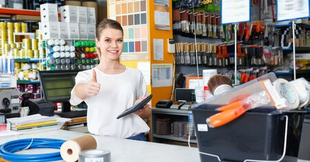 Young friendly pleasant female seller standing at the counter in household tools store 写真素材