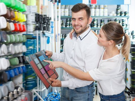 Ordinary man and woman  standing with tools using palette scheme in paint shop 写真素材