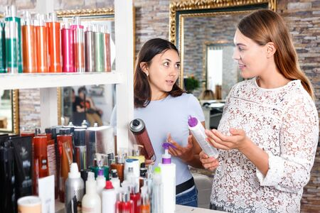Young glad cheerful positive women attentively looking hair care products at beauty salon