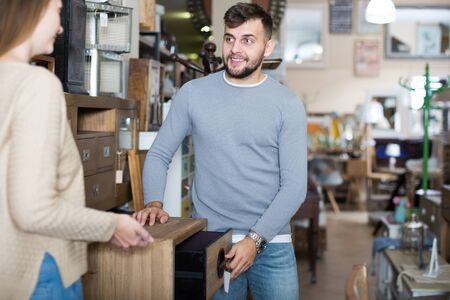 Young man with girlfriend choosing vintage bedside table in furnishings store