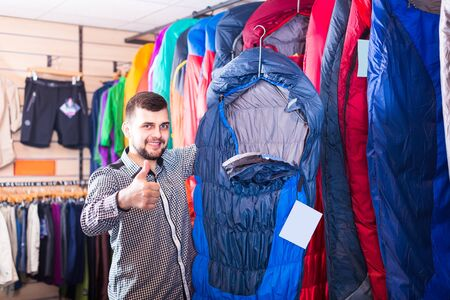 Smiling man recommends a sleeping bag for hiking in the sports equipment store