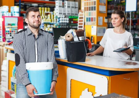 Positive man with purchases in household tools shop, woman seller standing at the counter
