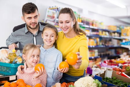 Happy parents with two girls choosing sweet citrus fruits in food store 写真素材