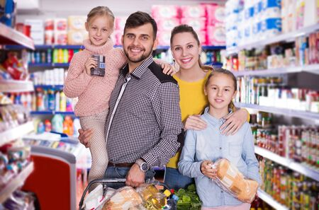 glad young  parents with two little girls with purchases during family shopping in grocery store