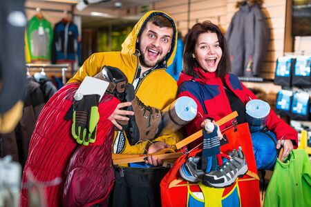 Young happy enjoying new tourist equipment in sports clothes store