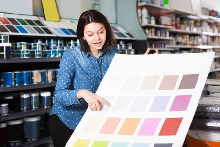 Girl is deciding on best color scheme in paint supplies store. Stock fotó - 131518062