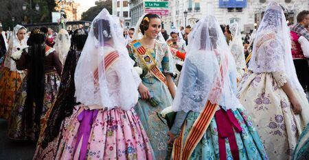VALENCIA, SPAIN - MARCH 18, 2019: Costumed procession in colorful traditional dresses in city streets on annual spring Falles festival
