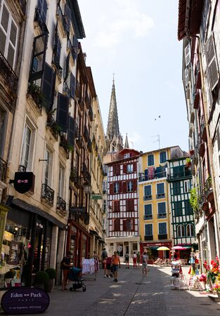 BAYONNE, FRANCE - JULY 17, 2019: View of traditional old narrow street with towering above it Gothic spire of Saint Mary Cathedral