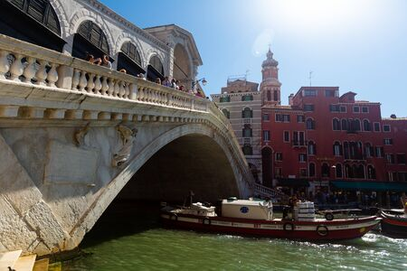 VENICE, ITALY - SEPTEMBER 05, 2019: View of famous pedestrian Rialto Bridge spanning Grand Canal in sunny autumn day