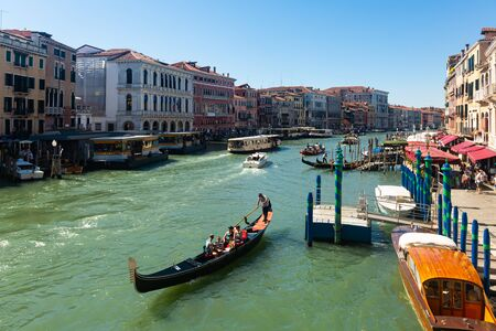VENICE, ITALY - SEPTEMBER 05, 2019: Picturesque Venice cityscape with Grand canal, moored boats, gondolas and ancient colorful buildings on banks of canal Sajtókép