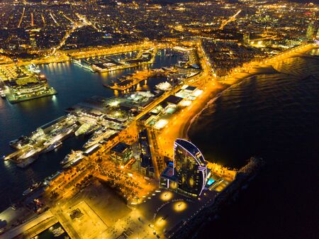 BARCELONA, SPAIN - MARCH 07, 2019: View from drone of illuminated Barceloneta beach with Port Vell and luxury hotel W Barcelona at night