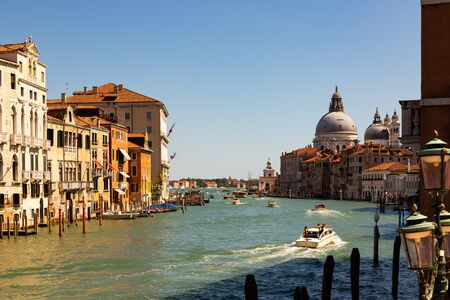 VENICE, ITALY - SEPTEMBER 05, 2019: Scenic view of Grand Canal with old colorful architecture of central districts and Baroque domes of Santa Maria della Salute in sunny day Sajtókép