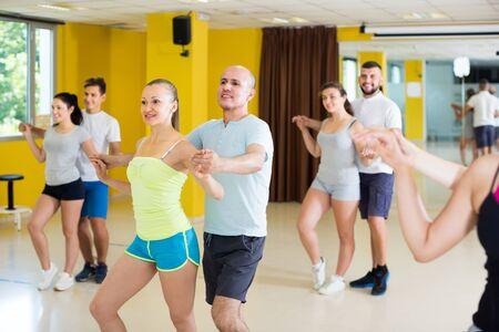 Positive dancing couples learning salsa at dance class 版權商用圖片