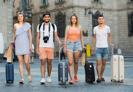 Group of tourists are walking together with luggage and looking on unfamiliar city. Banque d'images