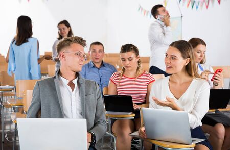 Feliz grupo de estudiantes adultos charlando animadamente mientras disfrutan del tiempo libre en clase