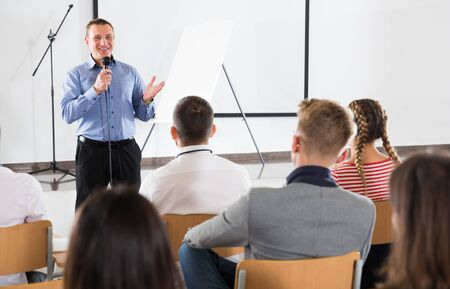 Positive male professor standing with microphone in auditorium, delivering speech to student group Stok Fotoğraf