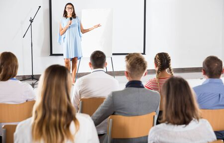 Confident female student answering with microphone in front of student group in auditorium