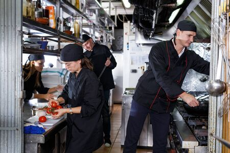 Cheerful cooks dressed in black uniform at restaurant kitchen 스톡 콘텐츠