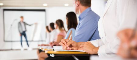 Woman making notes during lecture, focus on female hand with pen