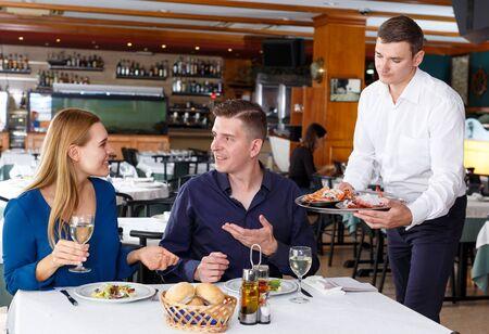 Friendly waiter serving tasty dishes – order of couple having dinner at restaurant