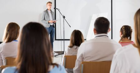 Focused male coach giving presentation for adult audience in lecture hall Stok Fotoğraf