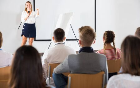 Friendly female teacher lecturing to attentive adult students at auditorium