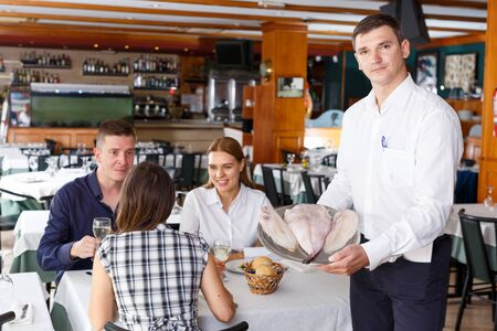 Waiter in white shirt showing tray of fish serving for group of visitors